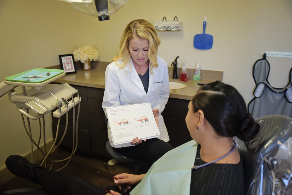Dr. Haterman consults with a patient about how a dental crown fits onto her normal tooth.